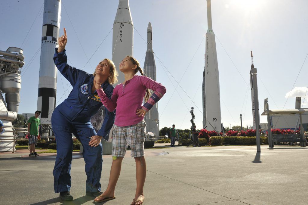 A female astronaut talks to a young girl at the Kennedy Space Center Visitor Complex