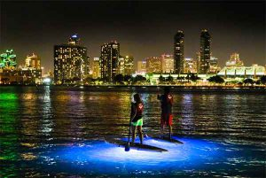A couple goes paddleboarding at night, which is among the best things to do in San Diego for couples