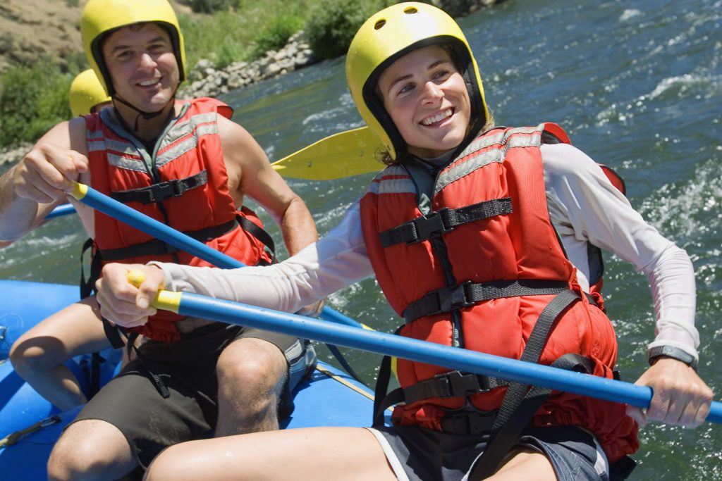 A man and a woman wear yellow helmets and red life jackets aboard a blue raft on the Pigeon River after planning a Gatlinburg vacation