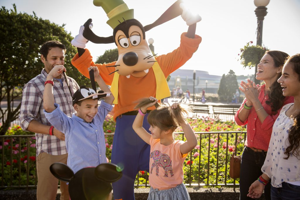 A family interacts with Goofy at Disney's Magic Kingdom theme park