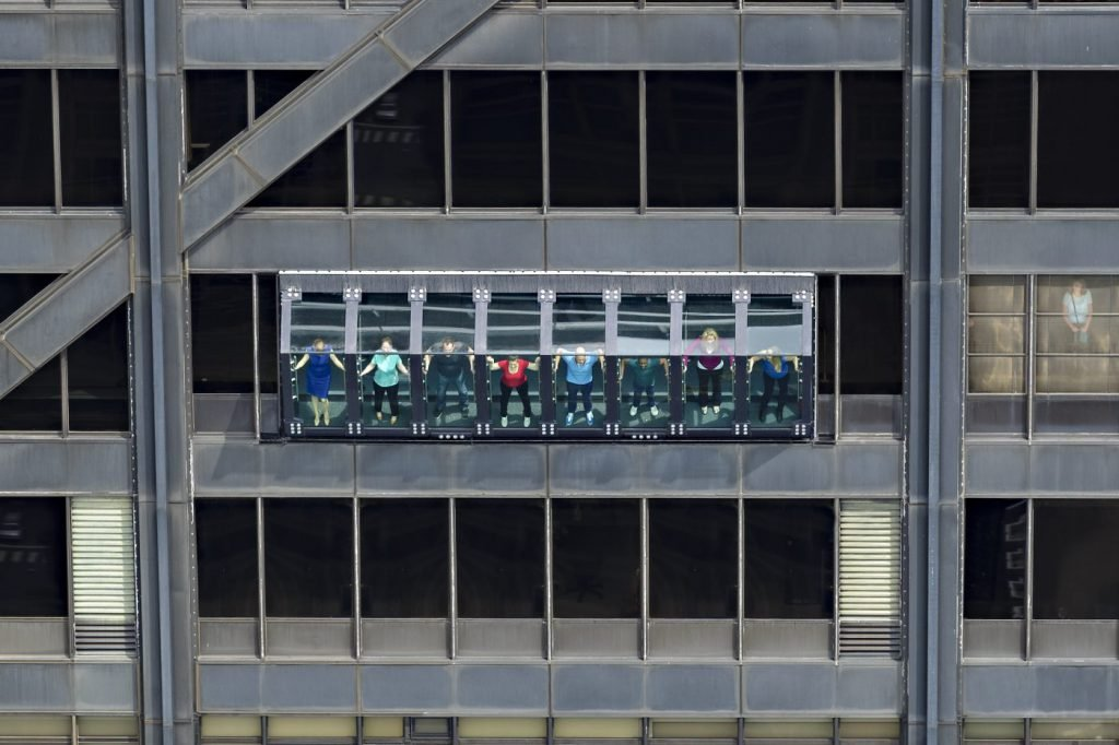 People lean out of the John Hancock Center on TILT at 360 Chicago