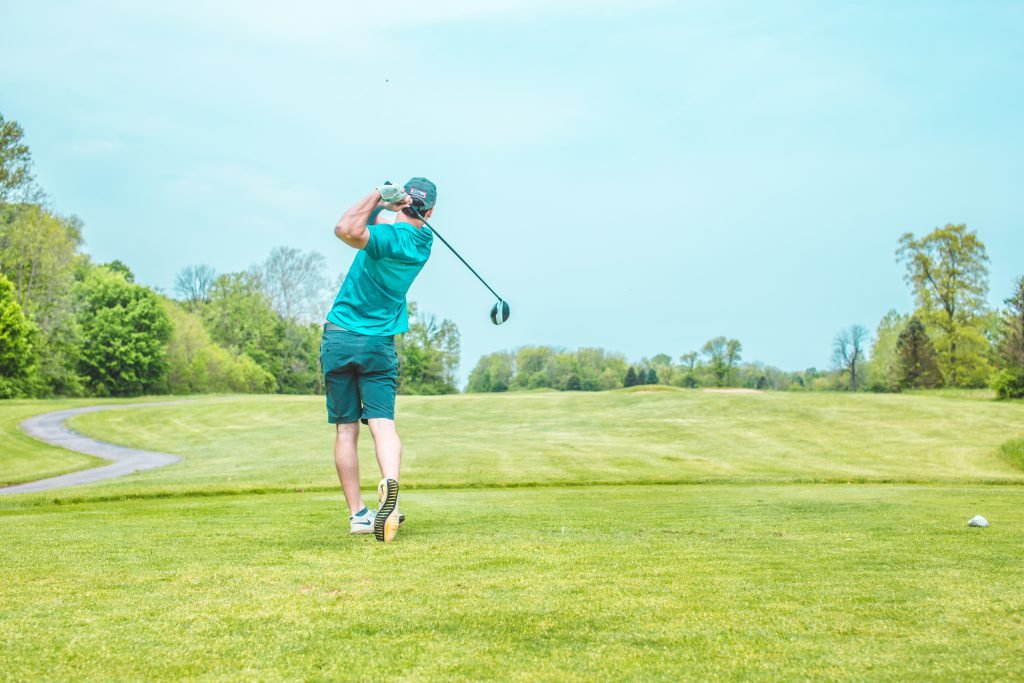 Man swings golf club on a course