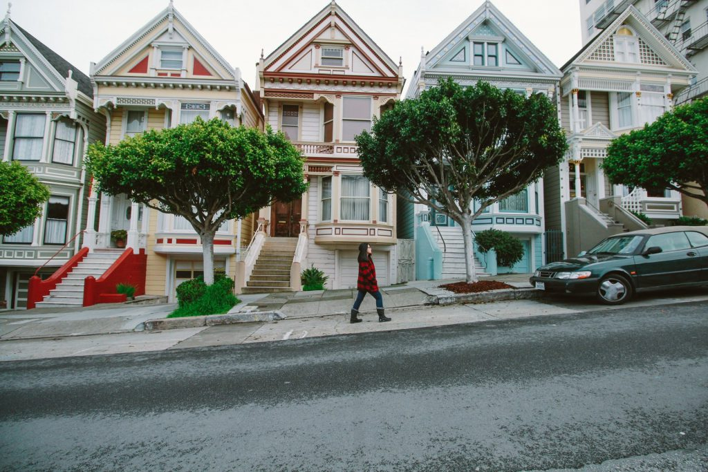 A woman in a plaid coat walks up the street past the iconic Painted Ladies houses in San Francisco