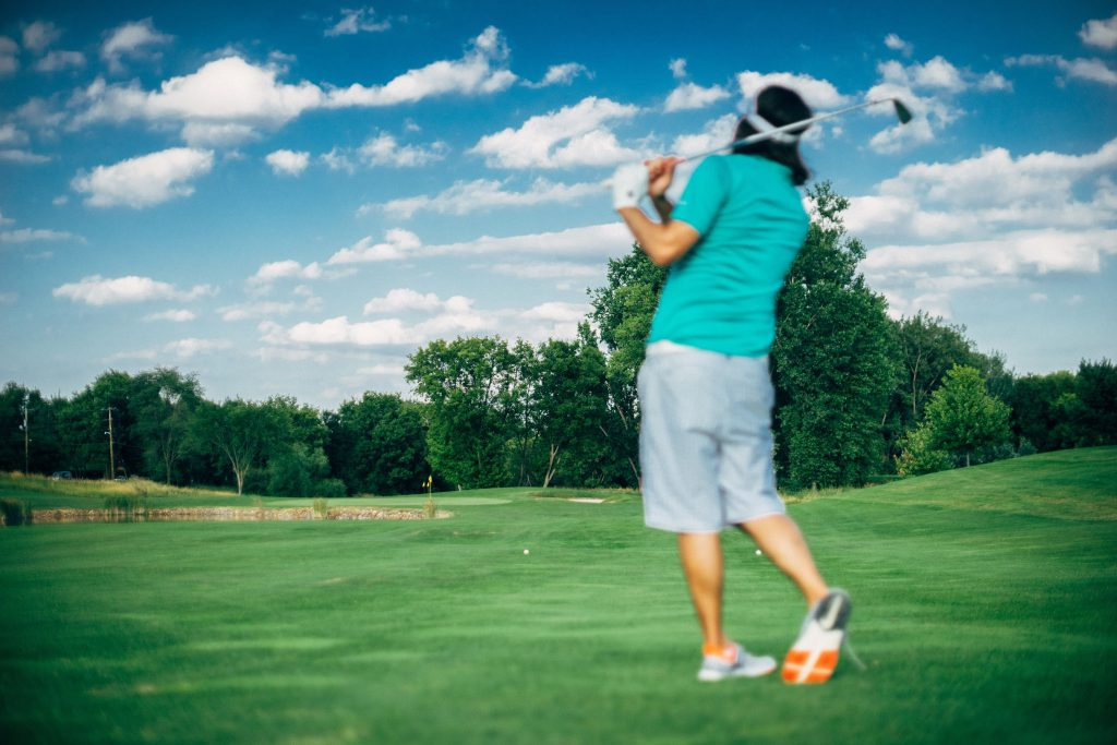 A man in a turquoise shirt swings a golf club