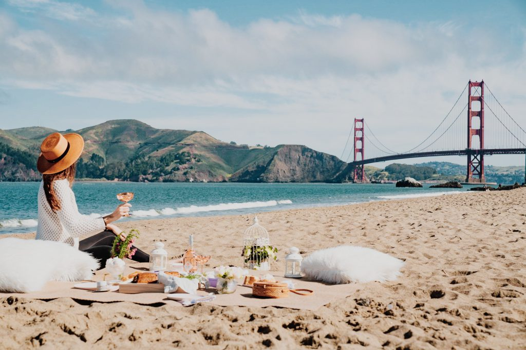 A woman in a white shirt, black pants, and a brown sun hat sits on the beach with a picnic with the Golden Gate Bridge and National Park area in the horizon.