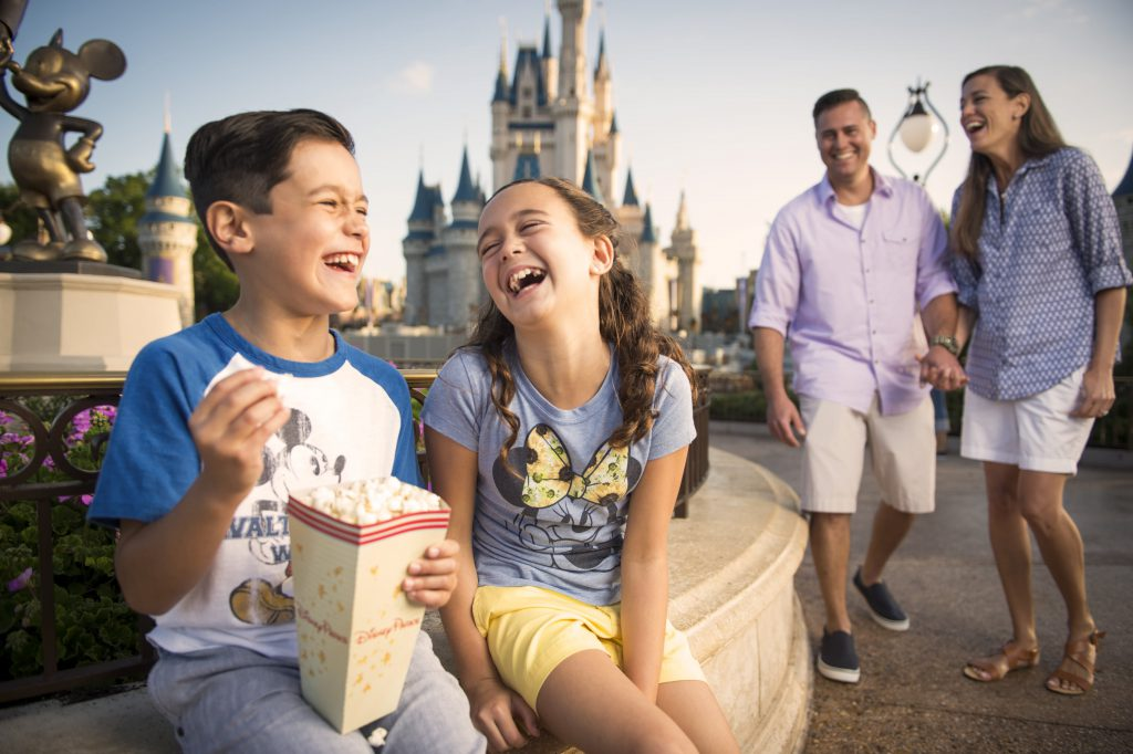 A family laughs together at Magic Kingdom, one of the best spring break destinations for families