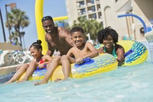 A family enjoys the pool at Beach Cove Resort, one of the Myrtle Beach hotels with free parking