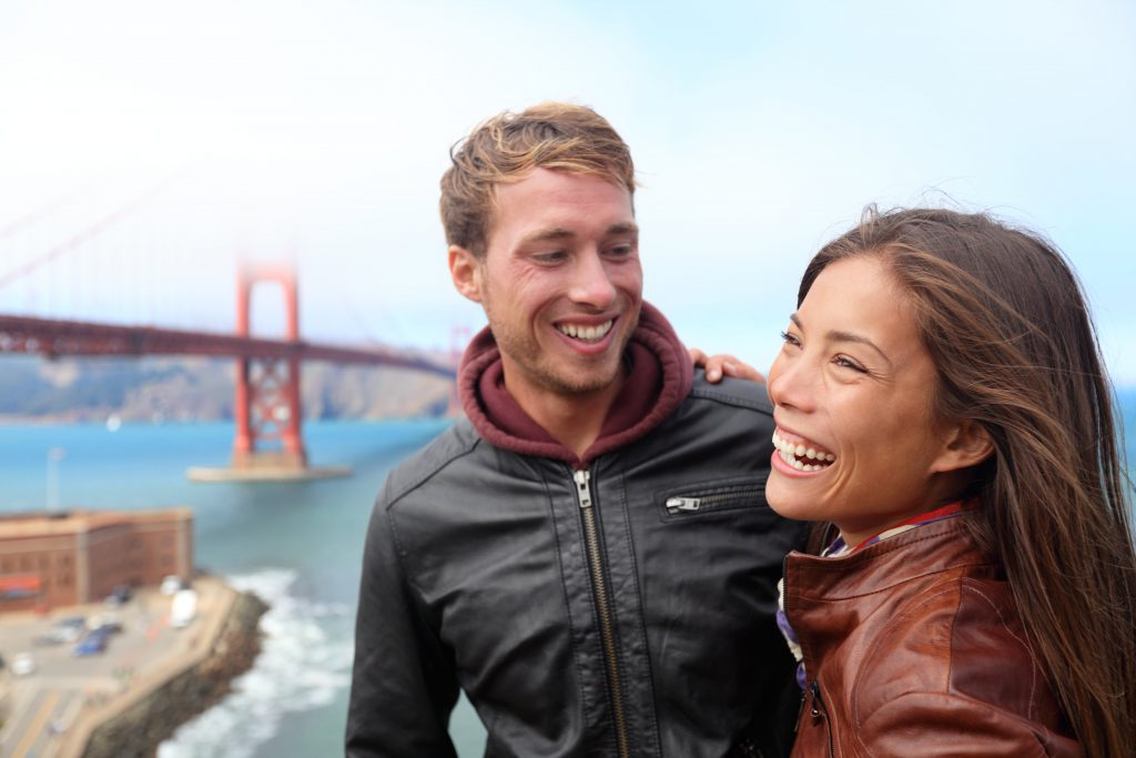A man and a woman smile in front of the Golden Gate Bridge on their San Francisco honeymoon