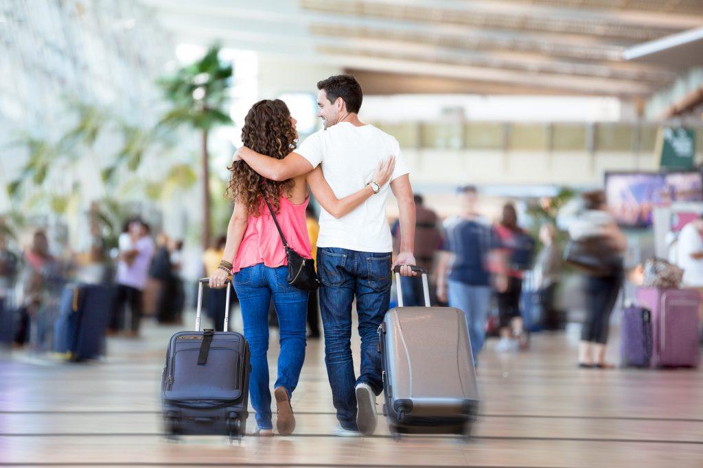A couple walk hand-in-hand through an airport on their San Francisco honeymoon