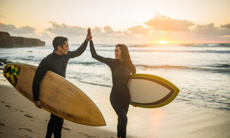 A couple high five while holding surf boards next to the ocean during a romantic weekend in San Diego