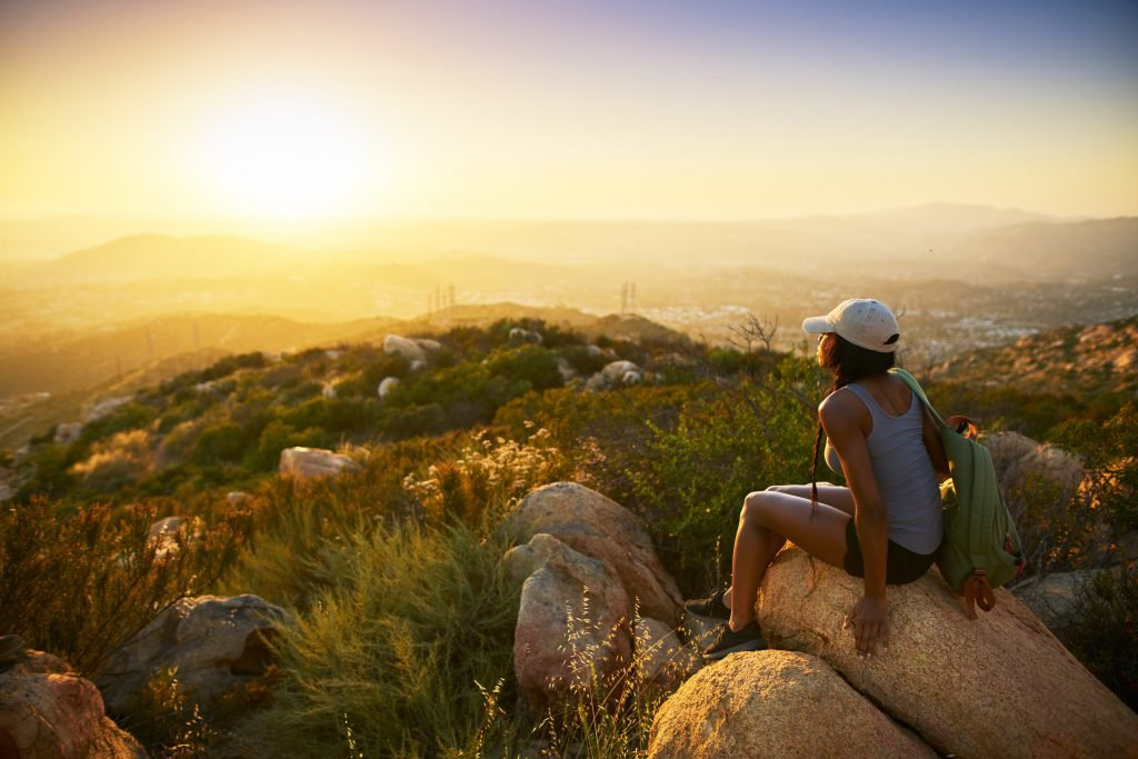 A girl looks at the sunset from a hiking trail on a weekend in San Diego
