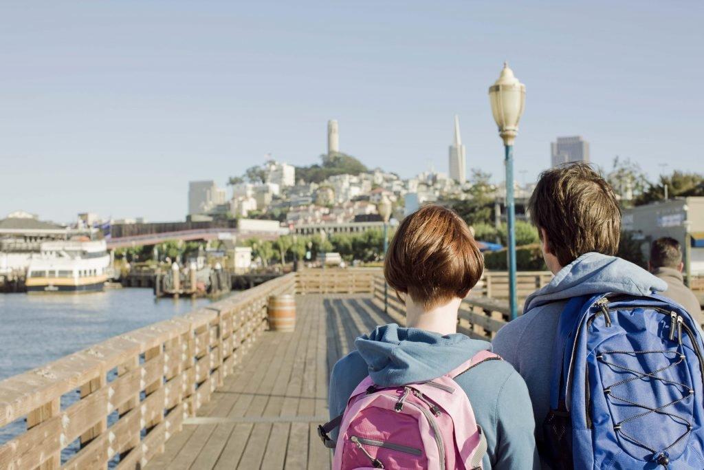 A couple walks towards Fishermans Wharf on their San Francisco honeymoon