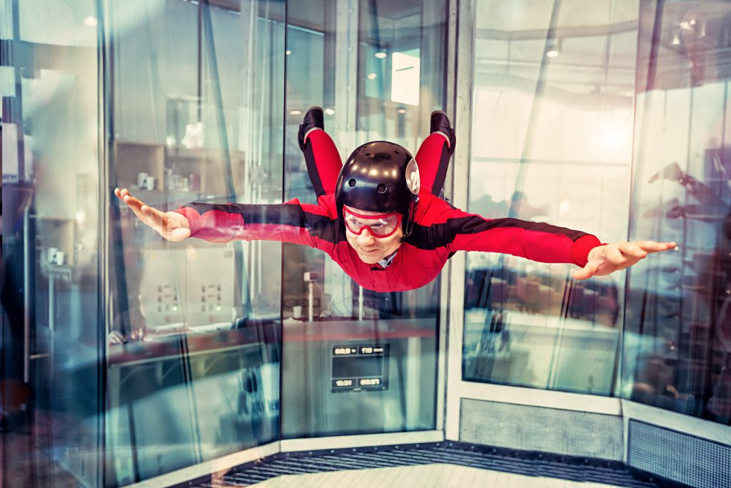 A man goes indoor skydiving in a red jumpsuit as part of the top things to do in Las Vegas during the day