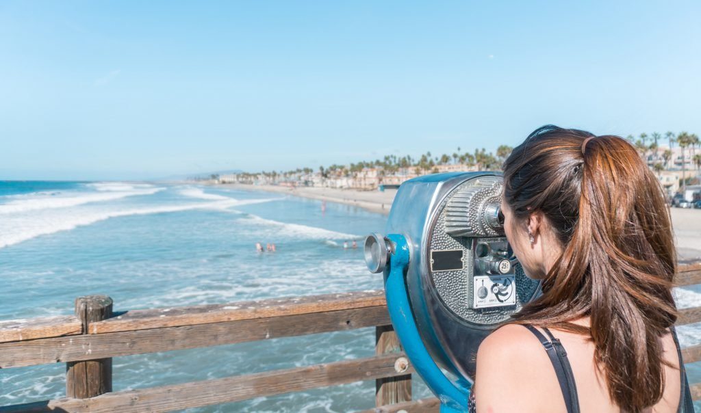 A woman stares through a view finder on the boardwalk while sightseeing on a weekend in San Diego