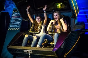 Two girls ride an attraction at WonderWorks during their Myrtle Beach spring break for families
