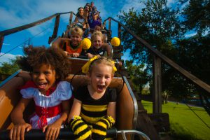 Kids ride a rollercoaster in Halloween costumes at LEGOLAND Florida
