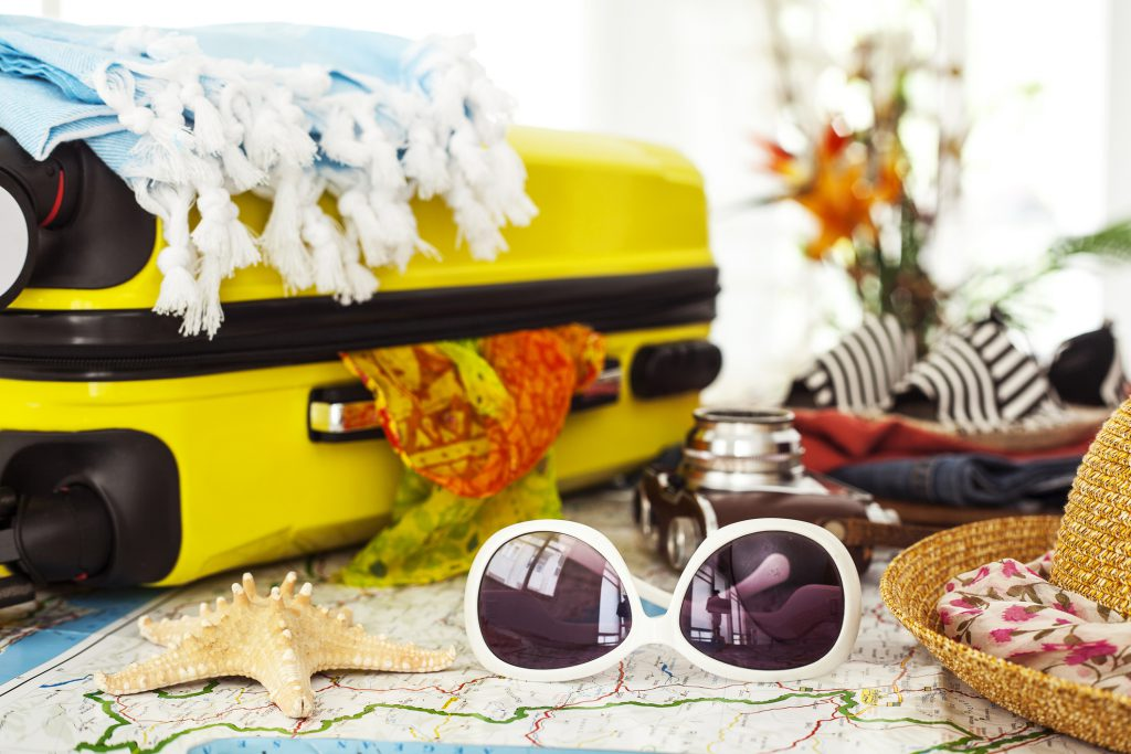 A yellow suitcase is surrounded by white sunglasses, a map, and hat getting ready to pack for a weekend in San Diego