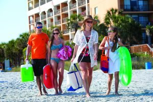 A family walks to the beach from the Caravelle Resort