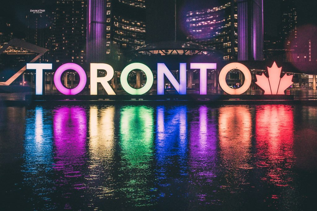 The rainbow Toronto sign is lit up at night reflecting against the water