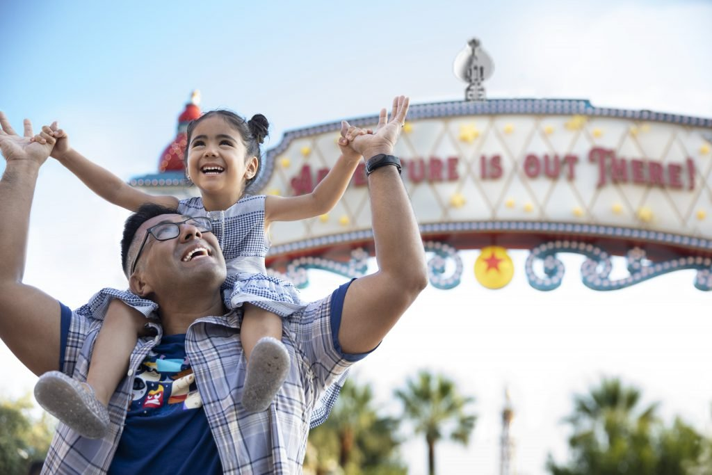 A daughter sits on her father's shoulders while they visit Disneyland on a budget