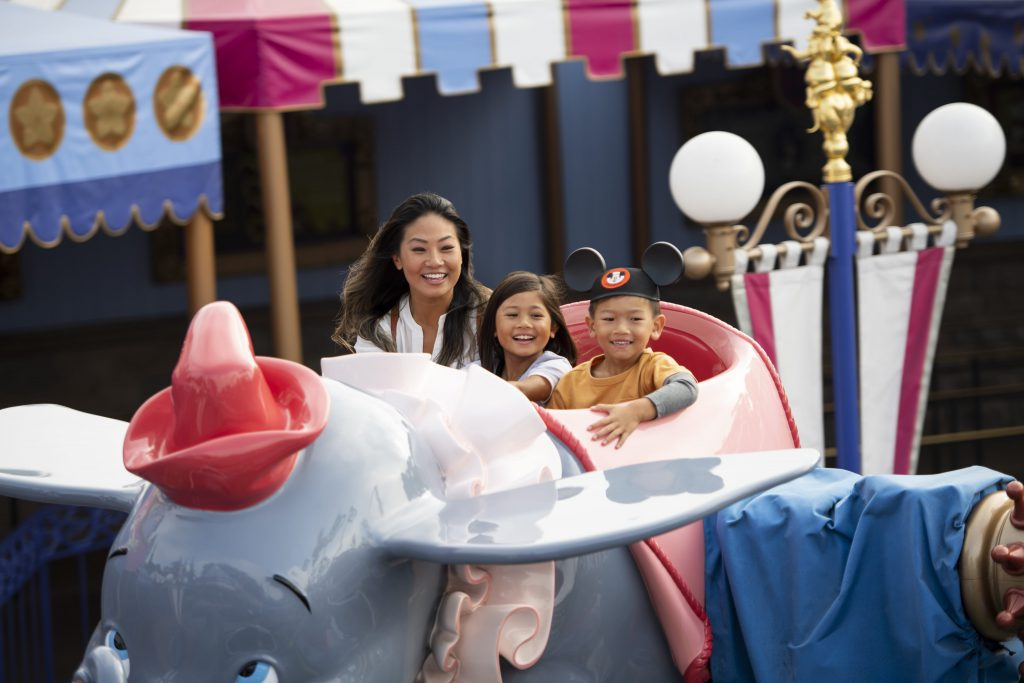 A family rides on the Dumbo ride while visiting Disneyland on a budget